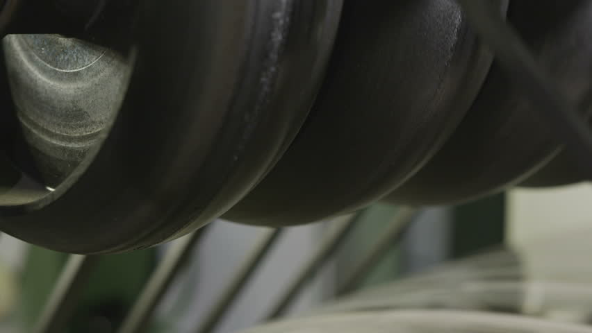 closeup thin rubber bands coiled slowly on green tires during modern tyre manufacturing process