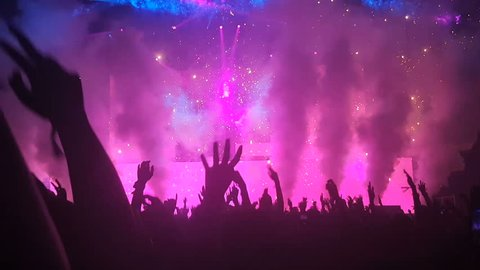 Happy people dance in nightclub party concert and listen to music from DJ on the stage in background. Cheerful crowd celebrate Christmas and New Year party 2018. Young people lifestyle and nightlife.