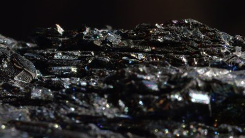 MACRO CLOSE UP: Vibrant Hematite with a glass like surface glimmering under rays of light. Dark brittle mineral with a metallic sheen. Polished form of iron oxide with powers to dispel negativity.