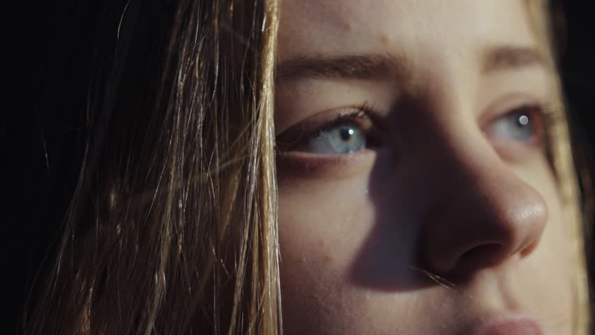 close up shot face young lonely sensual virgin european blue eyes girl room look morning sun light deep breathes in pure smell calm wind blowing Natural beauty