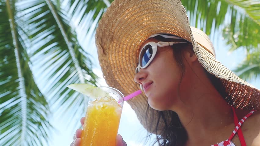 Pretty brunette woman wearing sunglasses and hat with tropical cocktail on the beach enjoying sunny weather in slow motion, 1920x1080 | Shutterstock HD Video #34890886