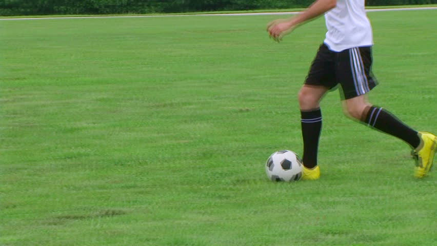 Young soccer player demonstrates footwork by dribbling ball