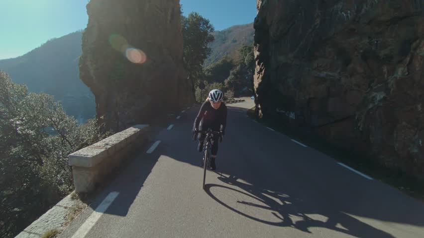 Slow motion action camera shot of inspiring female athlete, overcomes fear and sexism climbs up mountain road on professional racing carbon bicycle, looks determined and powerful