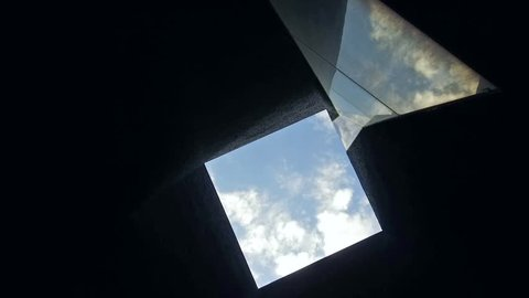Low angle shot of camera rotating in square ceiling. Abstract architecture detail. Blue sky background.