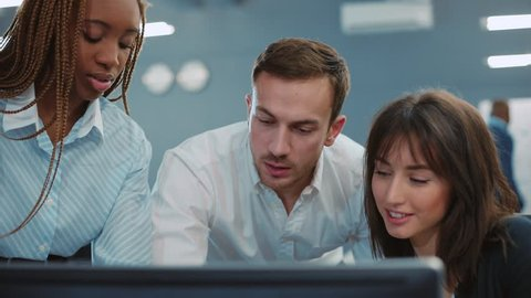 Three people standing at computer. Beautiful girl with African pigtails pressing key on keyboard and turning on video presentation. Young people smiling, talking. Office. Close-up.