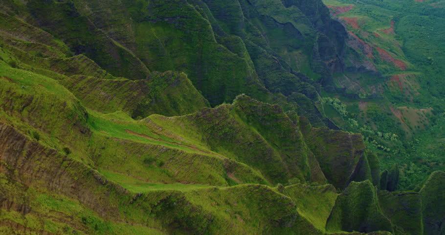 Cinematic aerial view of dramatic mountains and ocean on Napali Coast, Kauai, Hawaii