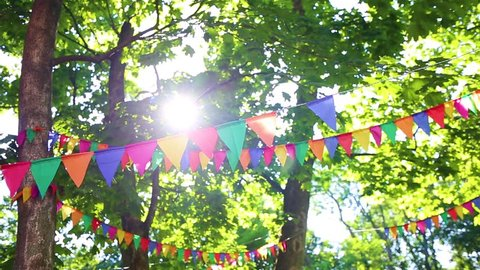 Colorful flags hanging on branches of trees as festive decoration for outdoor party. Bright summer sunshine among green leaves in background. Real time full hd video footage.