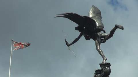 Beautiful Eros statue sculpture in Piccadilly Circus by day, national flag wave