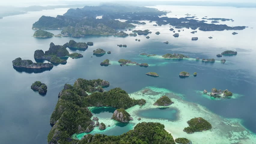 Aerial footage of beautiful islands and surrounding coral reefs in Raja Ampat, Indonesia. This remote, tropical area may contain the greatest amount of marine biodiversity on Earth.   Shutterstock HD Video #34960687