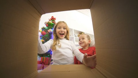 The happy kids open the box near the christmas tree