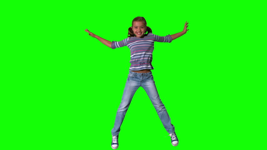 Happy girl jumping up and down on a green screen in slow motion #3497117