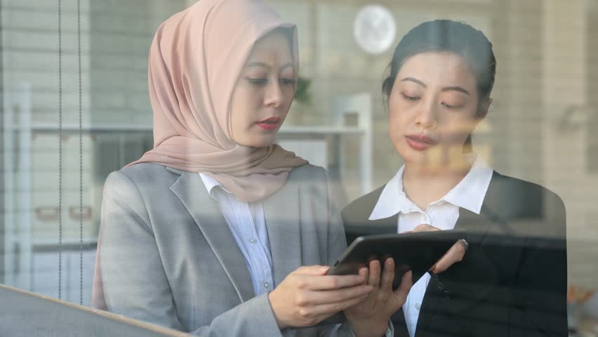Two colleagues muslim and Asian businesswoman meeting discussing project idea with digital tablet. image of shoot through from outside of the window | Shutterstock HD Video #34980943
