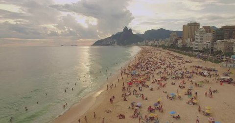 Low aerial shot of Ipanema Beach Rio de Janeiro Brazil with sunset and mountains in background