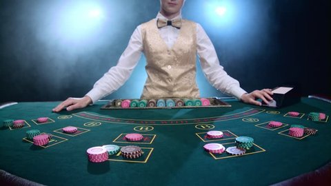 Croupier placing cards for poker on the table in casino. Smoke. Slow motion