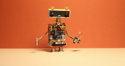 Comical robot handyman walks and shaking his arms. Toy robotic character with light bulb screwdriver. Orange wall yellow floor background