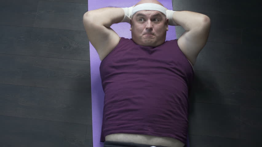 Funny overweight man doing crunches with great effort on mat, losing weight | Shutterstock HD Video #35028097