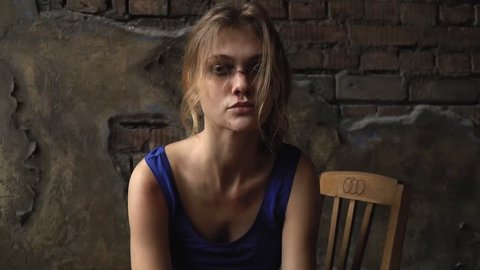 A girl with a broken face sitting on a chair pulls her hair back and embraces herself