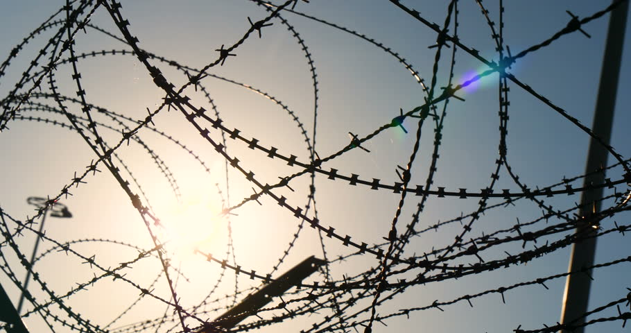 Sun set at Old Prison Yard With Barbwire Fence shot in 4K Ultra HD Slow motion close up security cameras.
