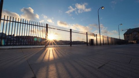 Beautiful embankment of typical European city with large fence. On the opposite shore beautiful white Nordic houses. Magnificent weather, beautiful sunset, sunshines, clear blue sky with white clouds.