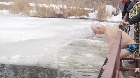 An elderly gray-haired man plunges into the ice water of an ice-hole. Hardening with ice water
