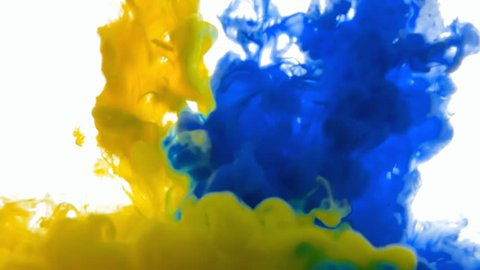 Blue and yellow ink streams pouring down in the water. Deep colors.