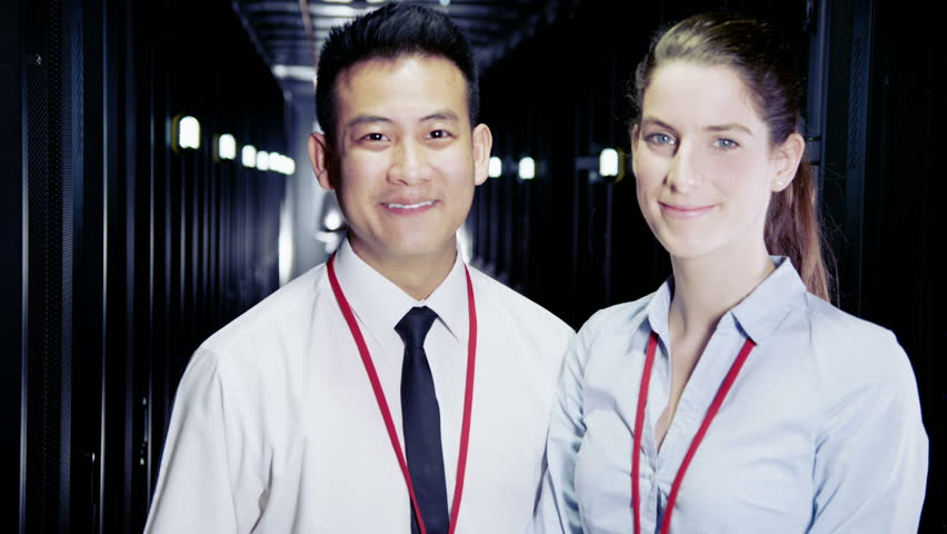 Two people of mixed ethnicity are working in a data center with rows of server racks and super computers. They are walking up and down and checking all of the equipment.  | Shutterstock HD Video #3511010