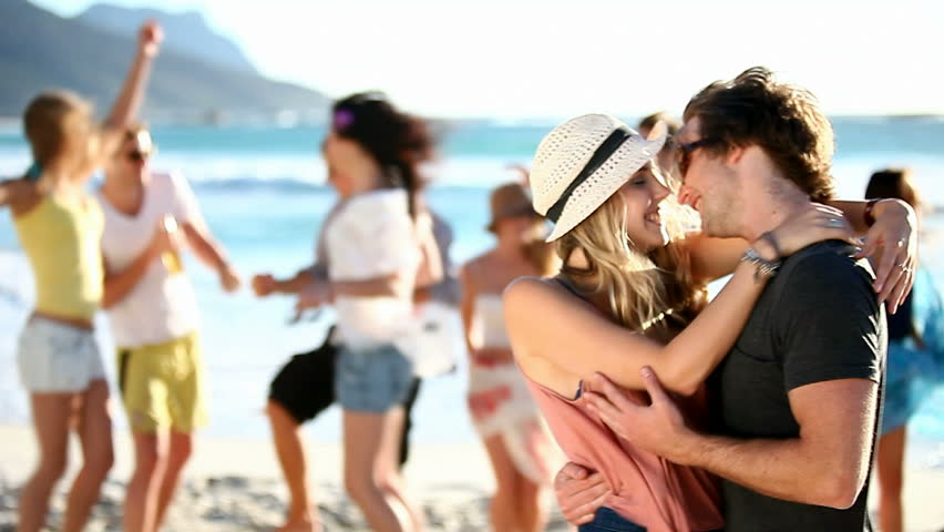 Hipster Friends having fun at the beach and a couple kissing in the front.