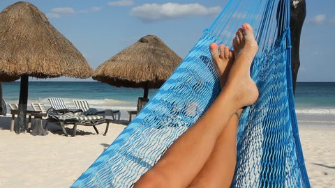 Hammock feet. Wide shot. Feet up in a hammock with palapas and tourist couple in the background. Tulum, Mexico.
