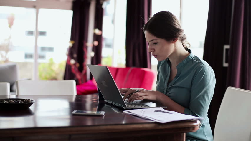 Young businesswoman working with documents and laptop in home