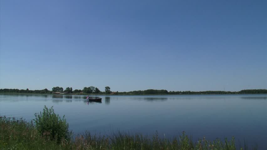 Small fishing boat on quiet blue lake + pan artificial Lake Oldambtmeer, Groningen, The Netherlands.