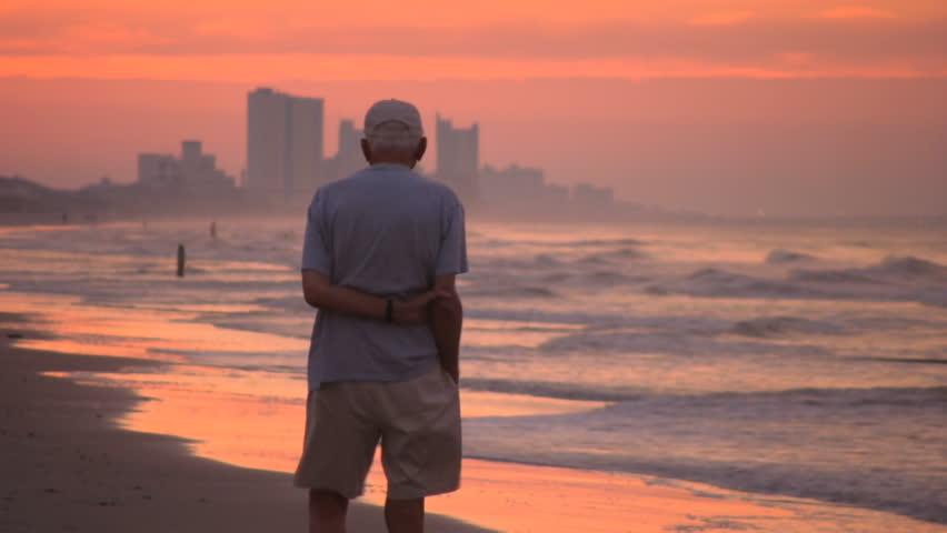 An elderly man walks alone on the Atlantic seashore at sunrise