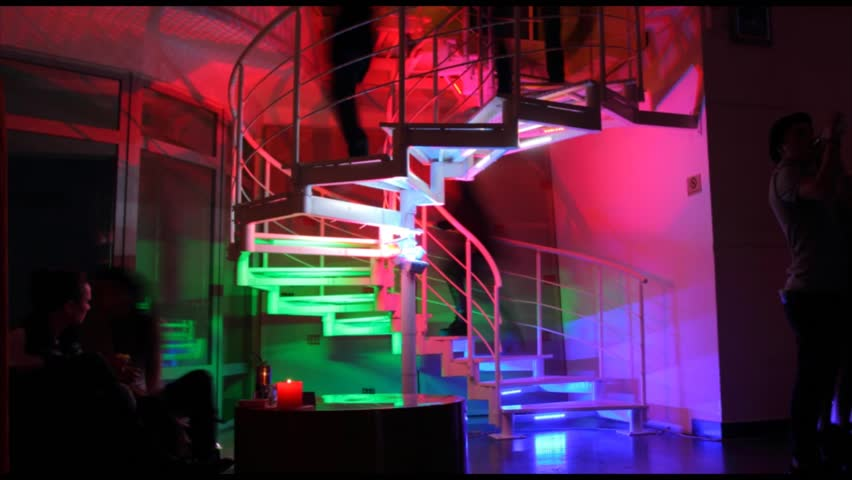 Timelapse of people going up the colorful stairs in night club