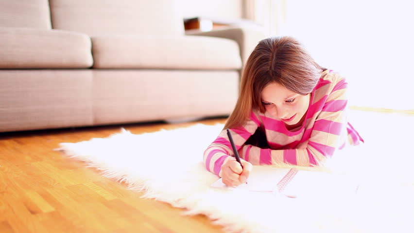 Girl Lying On Belly In Living Room Writing Her Diary And Looking Up Into