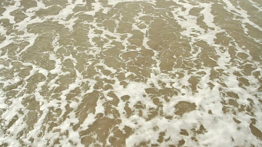 Tidewash Loop. Sea tide washes up a sandy shore and out again.  Loop-able clip. #3561797