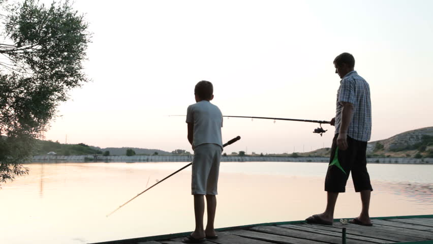 Father and son fishing at dusk