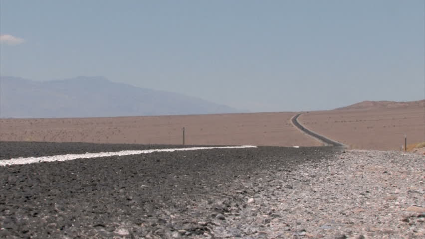Car in the background on a Highway winding through the Desert with heat haze on the pavement