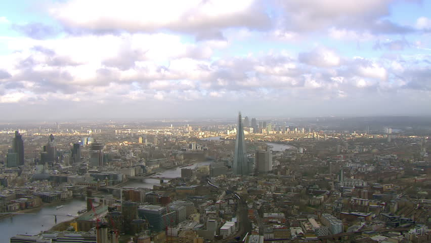 Stunning panoramic aerial view and cloudscape, flying over the city of London and the River Thames on a bright day