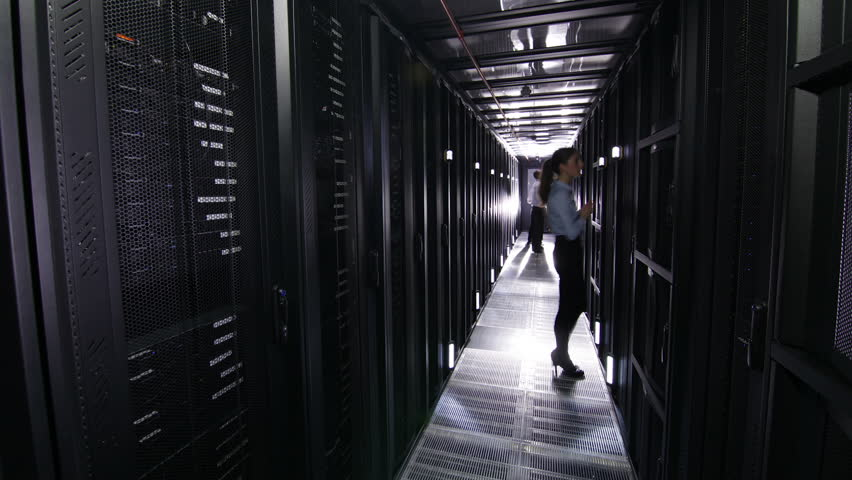 IT engineers carry out an inspection and maintenance procedure on servers in a dark data center. In time lapse