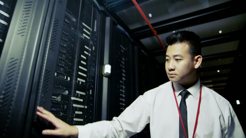 A young male IT engineer of Asian ethnicity is working in a data center with rows of server racks and super computers. He is looking into data cabinets and checking cables and other equipment.