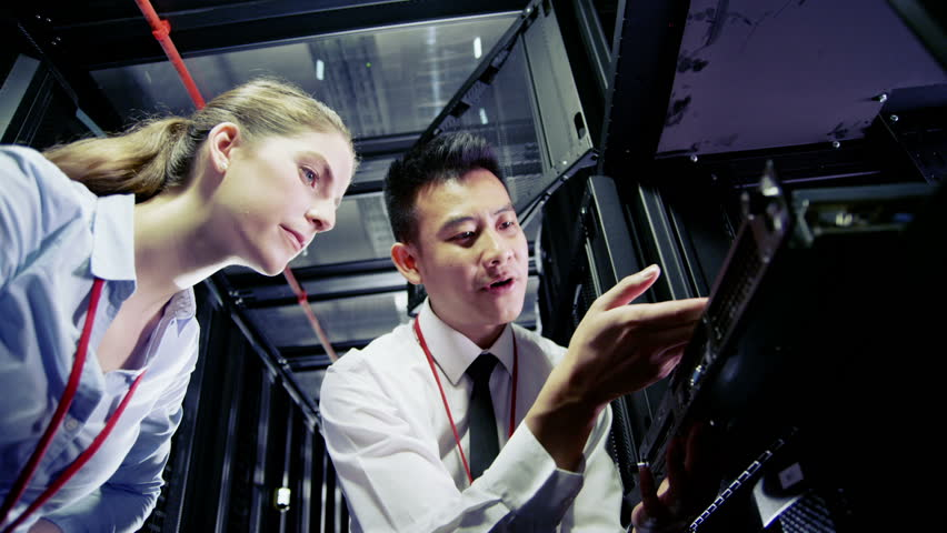 Two IT engineers are working in a data center with rows of server racks and super computers. They are discussing their work as they check cables and other equipment. In slow motion. | Shutterstock HD Video #3589157