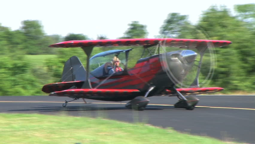Biplane taxis on runway and releases smoke.