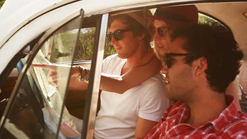 Young Hipster friends on a roadtrip looking at a map. | Shutterstock Video #3591233