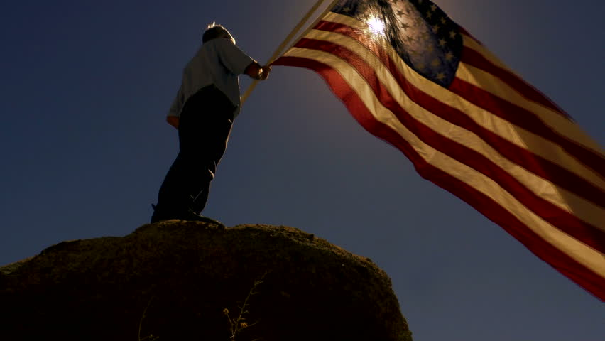 Man, silhouetted, lit by sun, stands on boulder, holds American flag that waves in strong wind, slow motion. 1080p