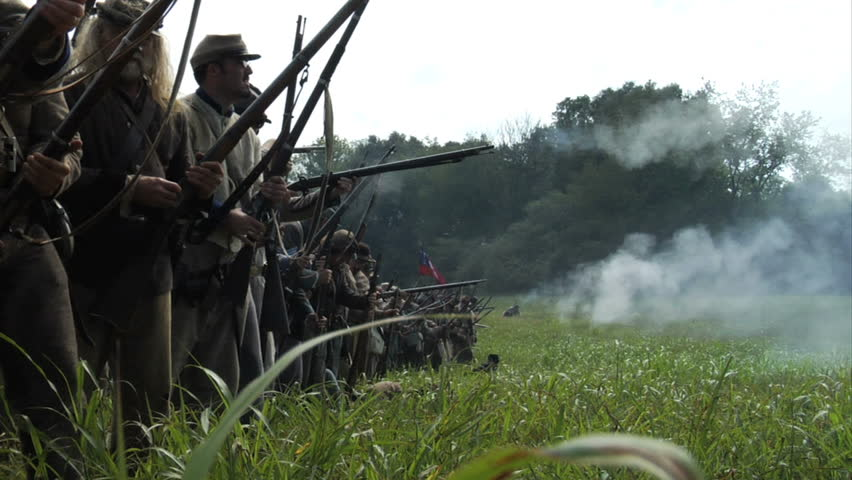 GEORGIA - OCTOBER 2008 - large-scale, epic Civil War anniversary reenactment -- in the middle of battle.  Line of Confederate infantry fires at will in line of battle as men try to rescue the wounded.
