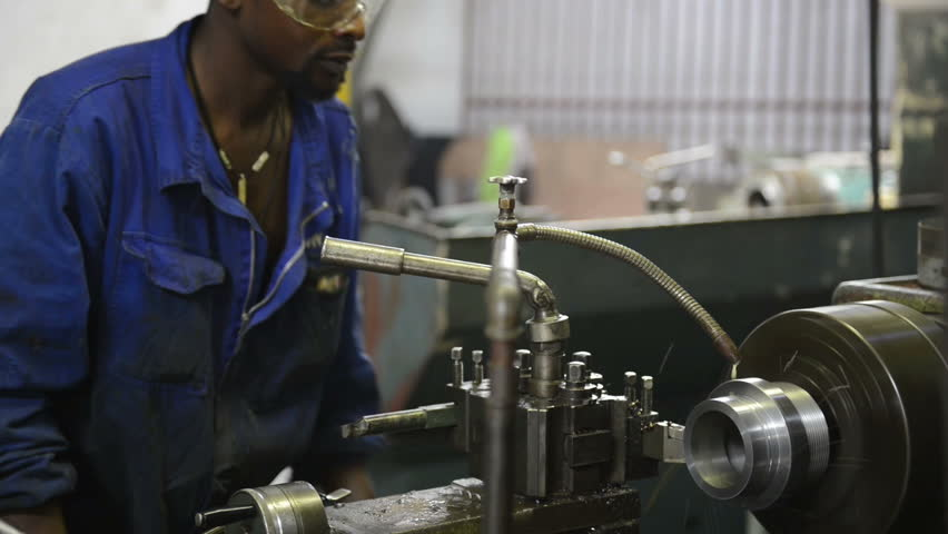 An industrial service repairmen labouring in workshop, selective focus, working on industry machine