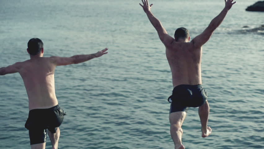 Young men jumping, swimming in the sea, slow motion shot at 120fps