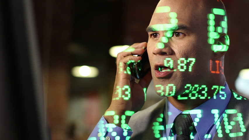 Happy and positive stock trader on the phone with ticker symbols projected