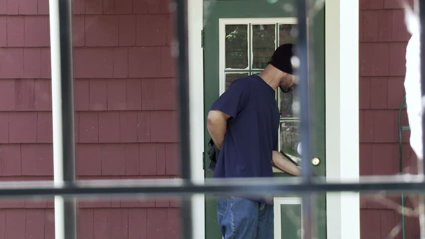 Burglar makes his way up to a house door, finds it locked and tries to open it
