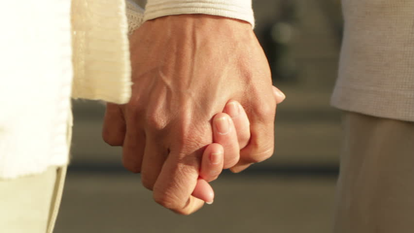 Senior asian man and woman hold hands, big close up with some camera movement.