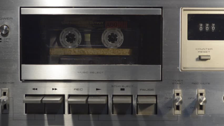 Close up to a cassette tape deck when a finger start and stop playing.